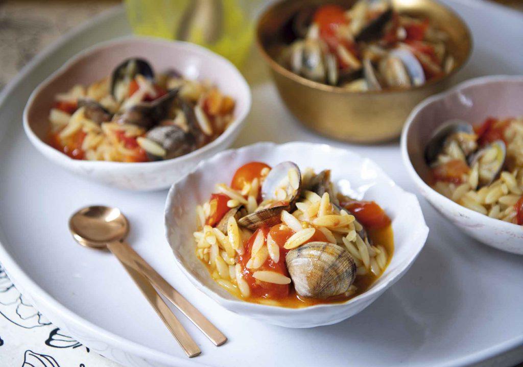 Almejas con jitomate y harissa y pasta orzo con azafrán